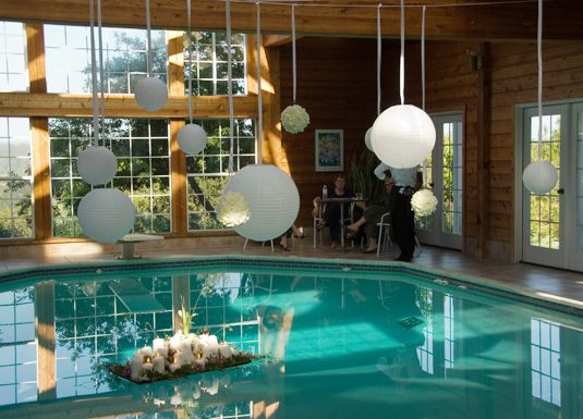 Poolhouse at the wedding decorated with white paper lanterns and floral spheres
