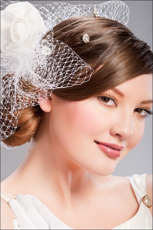 White netting swirled through chignon with rhinestones sprinkled throughout hair