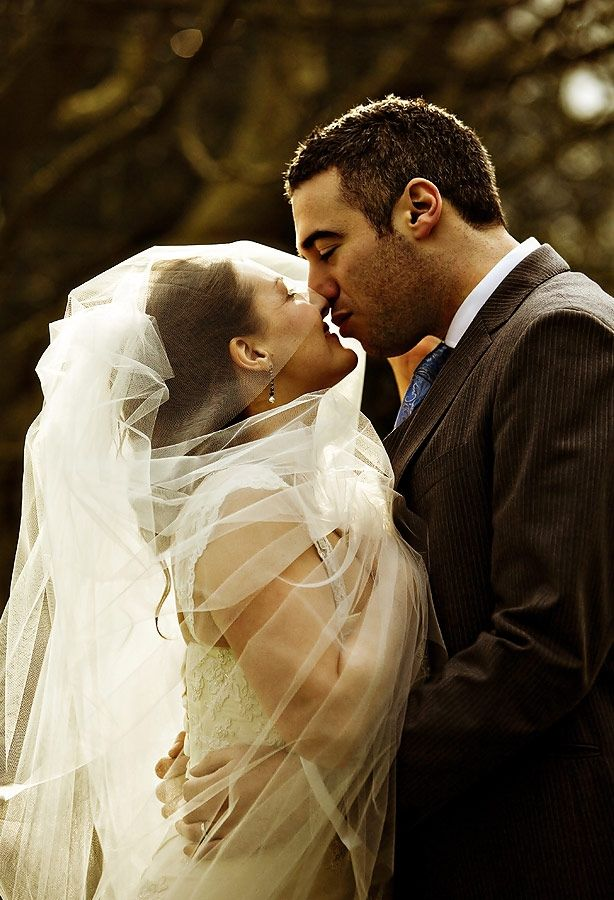 Bride in white wedding dress and veil is held by groom, kiss lovingly