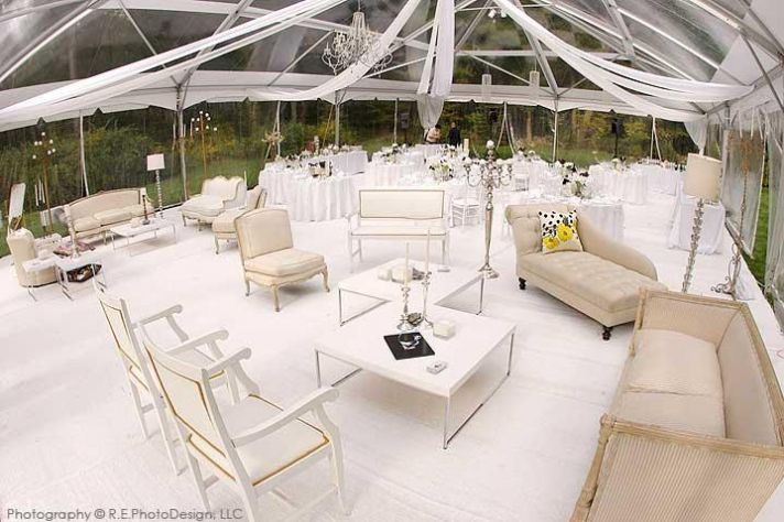 Stark white wedding reception under tent, white and ivory chairs, lounges, and more