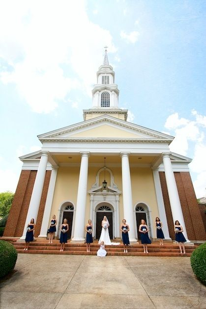 Bride in white dress with veil, bridesmaids in blue, short dresses stand in front of yellow church.