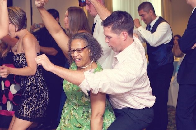 Wedding guests dance enthusiastically.