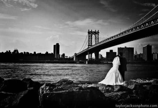Black and white photo of bride and groom standing beneath San Fran's Golden Gate Bridge