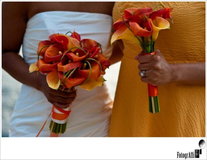 The orange and yellow calla lillies are the perfect flowers for the yellow bridesmaid's dress and th