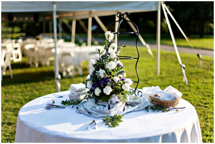 Gorgeous backyard wedding, with white tent and tables, white, purple and green floral centerpieces