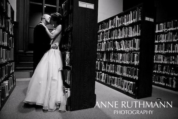 Romantic black and white wedding photo- bride and groom kiss against book shelves at library