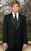 This handsome blond groom wears a black two-button tuxedo with silk lapels and a black silk tie and
