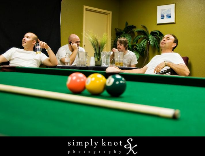 Groomsmen relax around the billiard table while the girls get ready for the wedding