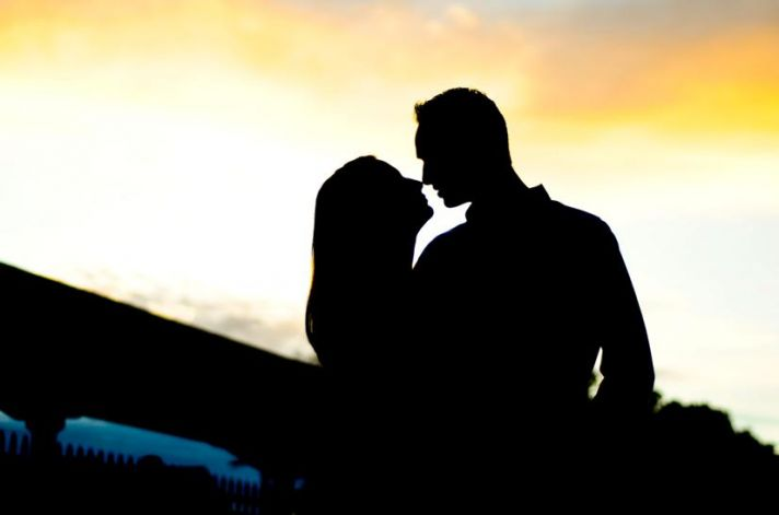 Artistic silhouette engagement photo with Florida sunset as backdrop