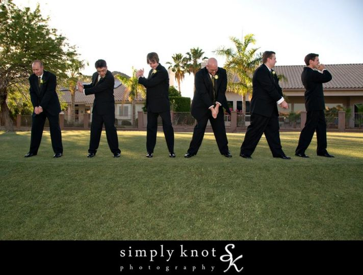 Groom and groomsmen pose in best golf positions, while wearing wedding day garb