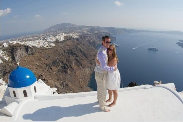 Bride and groom pose atop white washed villa in Santorini