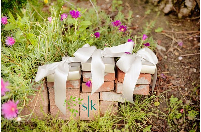 Guests' wedding favors tied with pretty white ribbon sit atop bricks outside