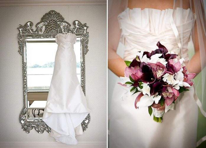 Brides white strapless wedding dress hangs on elegant silver wall mirror; purple, pink, and white br