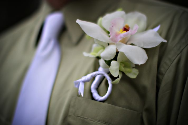 This groom is wearing a tan shirt, white tie and white orchid boutonierre.