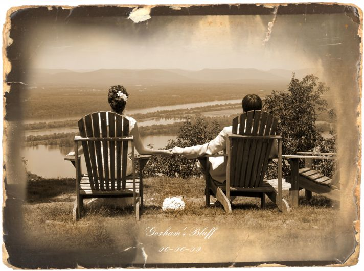 This bride and groom sit outside in comfortable wooden chairs, awaiting their future.