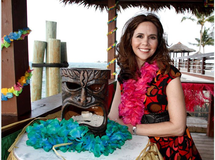 Festive luau-themed rehearsal dinner with flaming tiki masks, colorful leis, floral garland, and raf