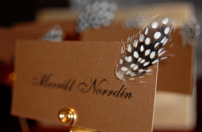 adorabe-chic-wedding-detail-gold-escort-cards-with-black-caligraphy-arorned-with-black-white-spotted-feather