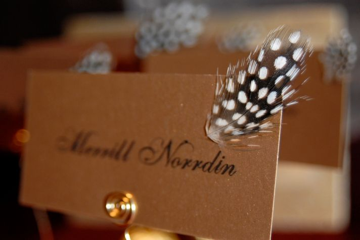 Chic and glamourous gold escort cards with black cursive and black and white spotted feathers