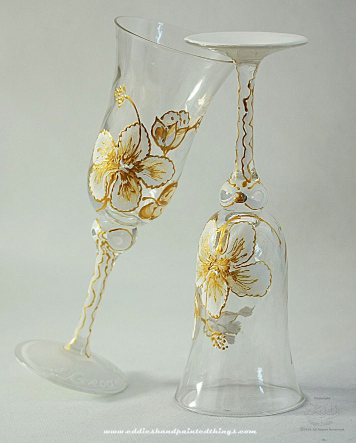 Custom hand painted toasting flutes featuring a white and gold hibiscus design