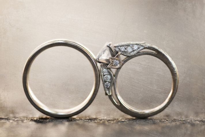Platinum wedding band touches bride's diamond engagement ring in this artistic wedding photo