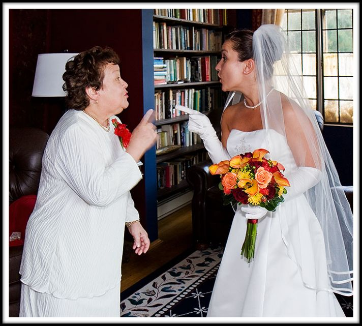 A bride in a beautiful white wedding dress with orange and red flowers argues with her mother who is