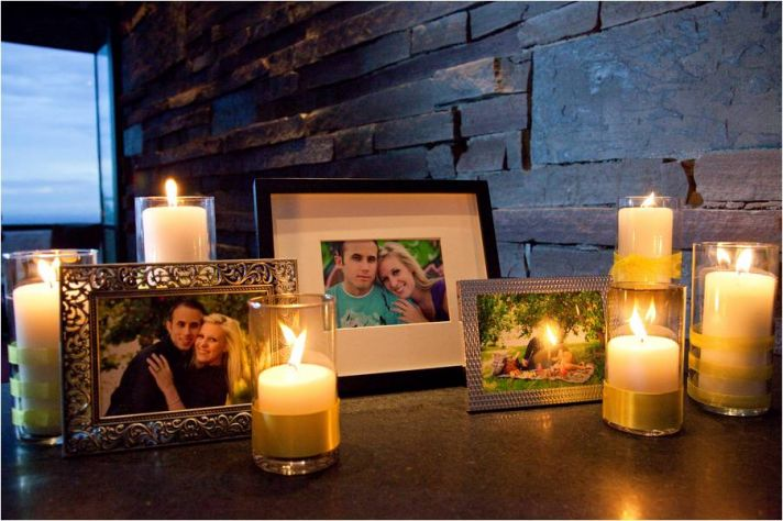 Escort table at wedding reception with framed photos of the couple, and romantic pillar candles