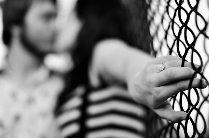 Bride holds fence while kissing groom passionately, shows off diamond engagement ring
