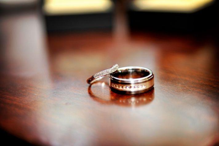 Artistic engagement ring wedding band photo, captured on dark mahogony