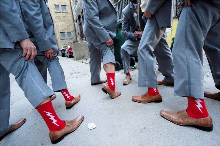 Groomsmen wear grey suits, show off funky red socks