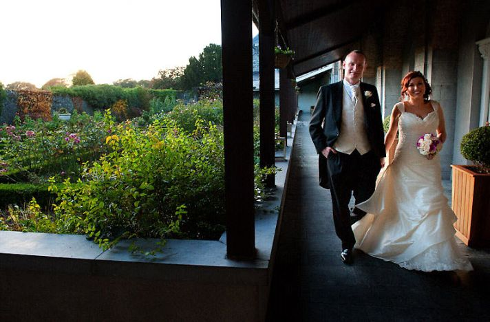 Bride and groom walk outside, hand in hand, after saying I Do