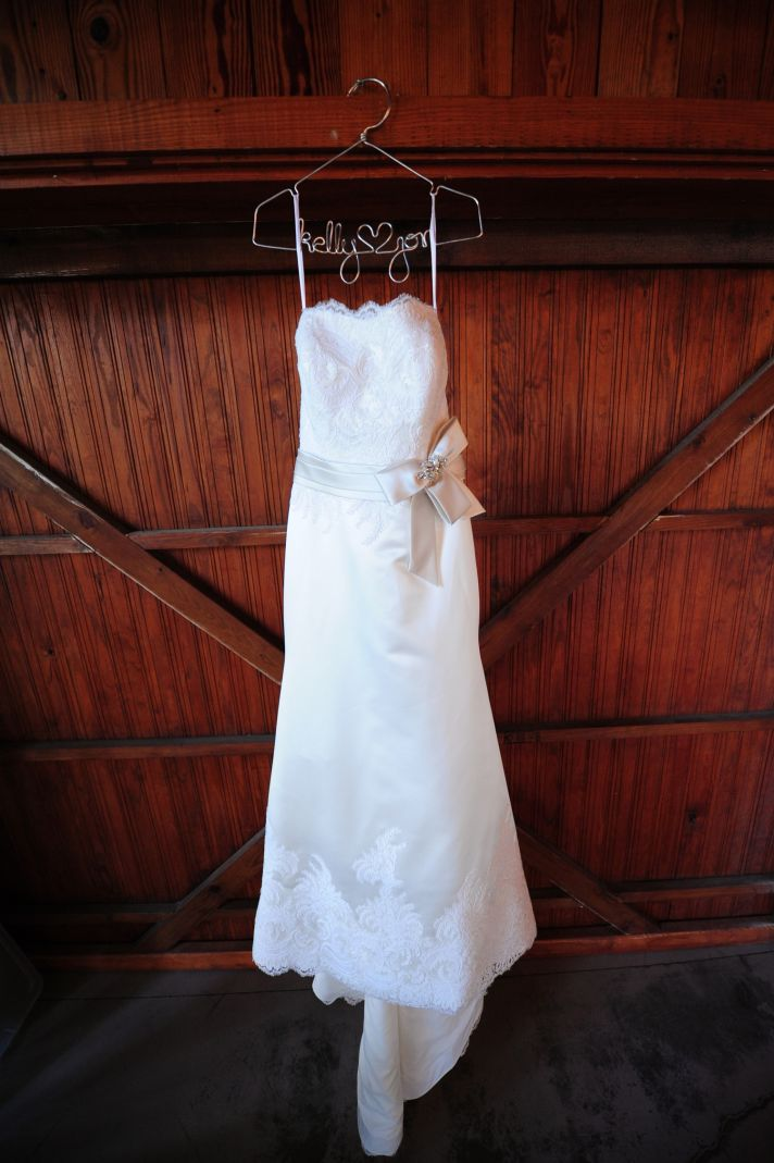 Romantic ivory lace strapless wedding dress hangs inside South Carolina wedding venue