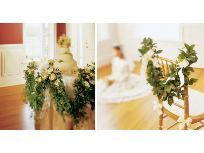 Elegant green garland accented with ivory roses adorn wedding cake table