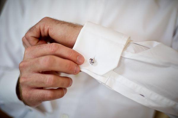 Groom puts on wedding cuff links