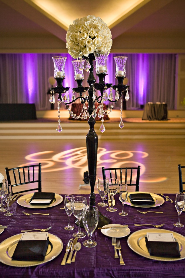 Ivory roses atop black candelabra draped with crystals at chic wedding