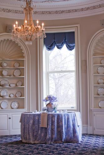 Elegant wedding reception venue with sparkling chandelier blue lilac ivory