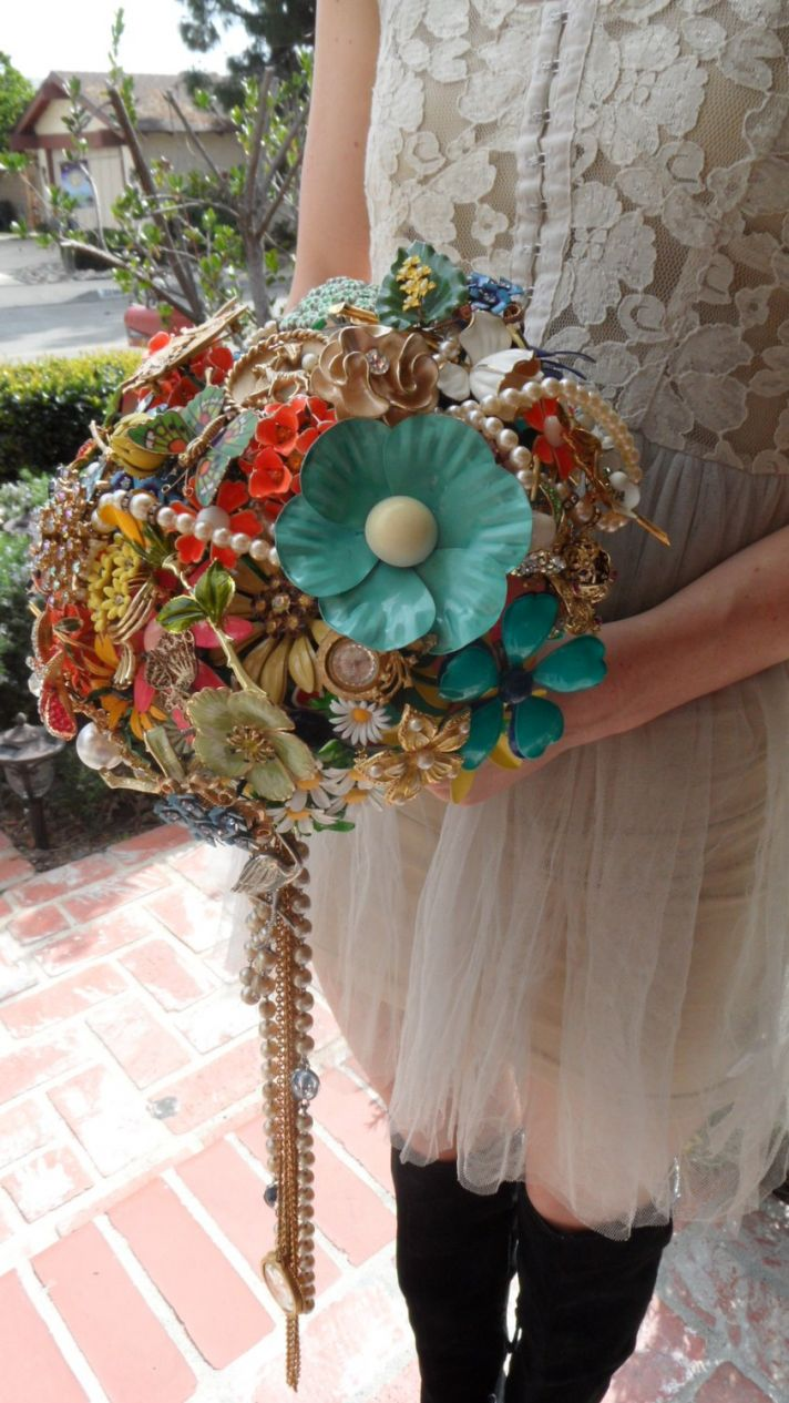 Offbeat vintage bride holds antique bridal brooch bouquet