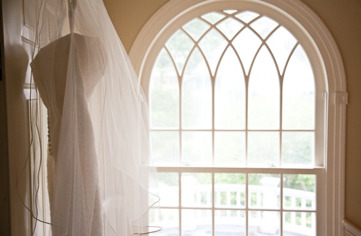 elegant real wedding outdoor reception under tent wedding dress hangs in window