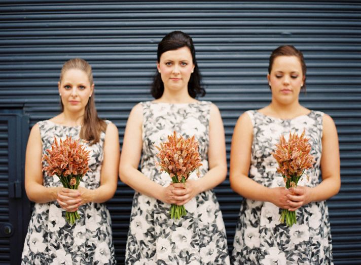 black white printed bridesmaids dresses orange bouquets