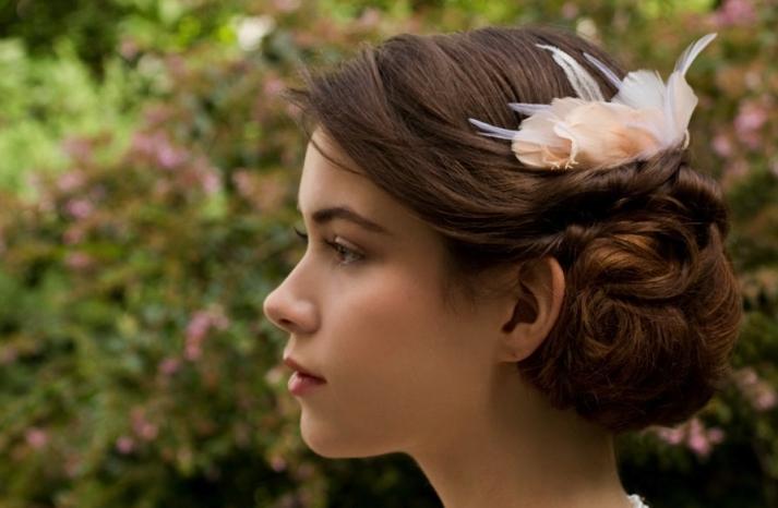 Elegantly twisted wedding hairstyle with fascinator