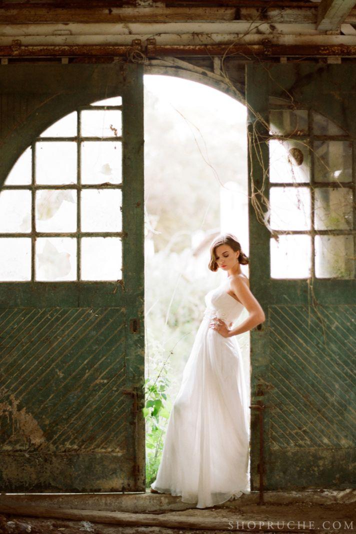 Romantic bride poses in rustic barn