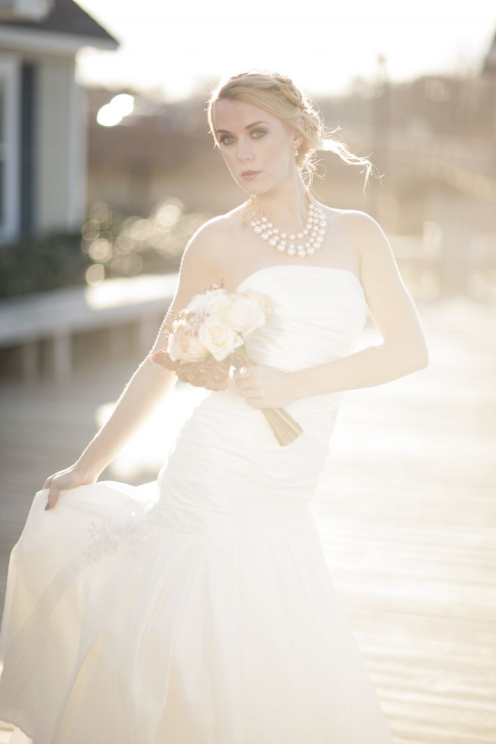 Romantic bride poses outside on dock, cushion cut engagement ring