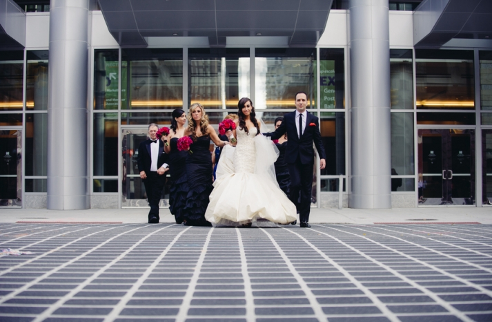Bride and Groom walk to venue with wedding party
