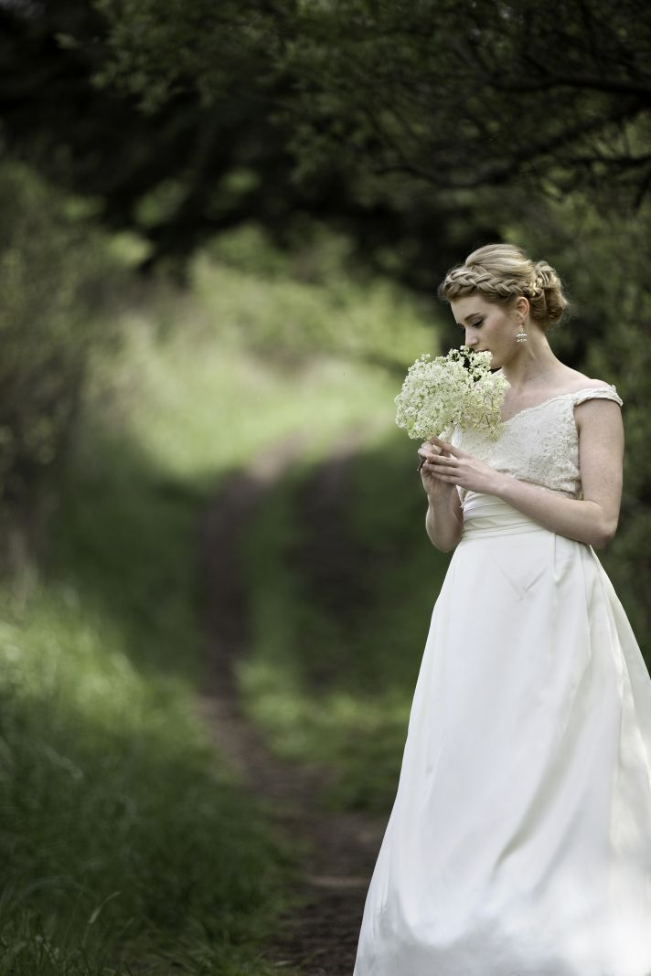 Classic bride wears ivory wedding dress braided hairstyle