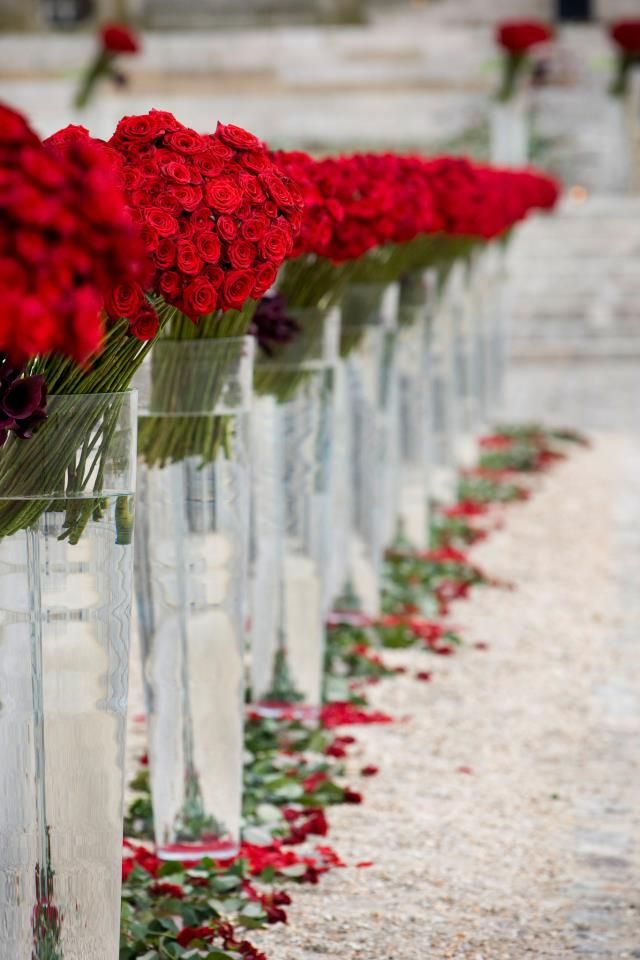 All red wedding flowers lining ceremony aisle