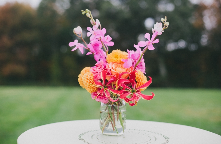 exotic wedding centerpiece with bright orchids and orange blooms