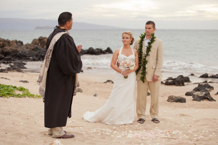 Intimate wedding on the beach exchanging vows