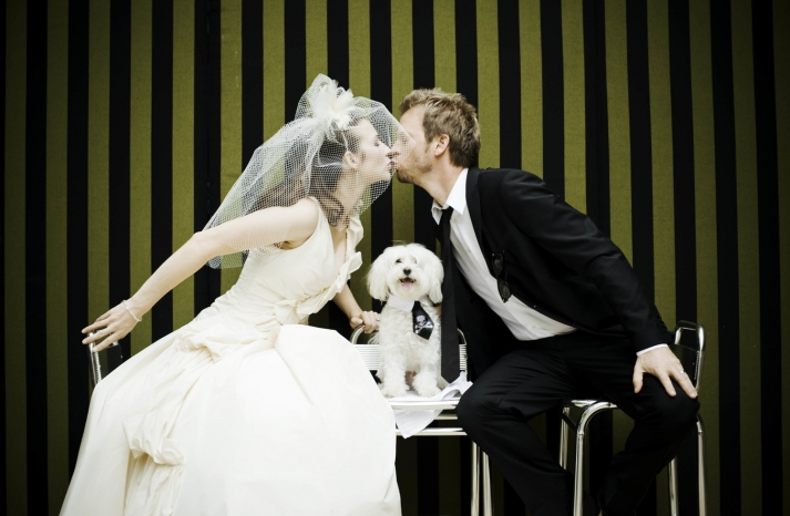 Bride and groom kiss with striped green and black backdrop