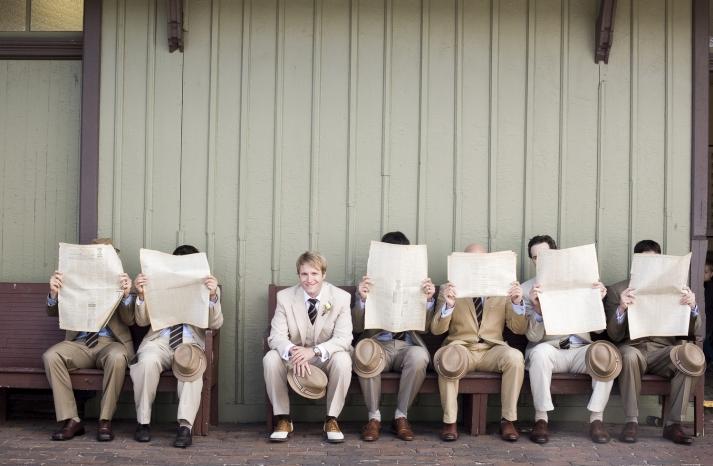 Groomsmen pose with groom behind vintage newspapers