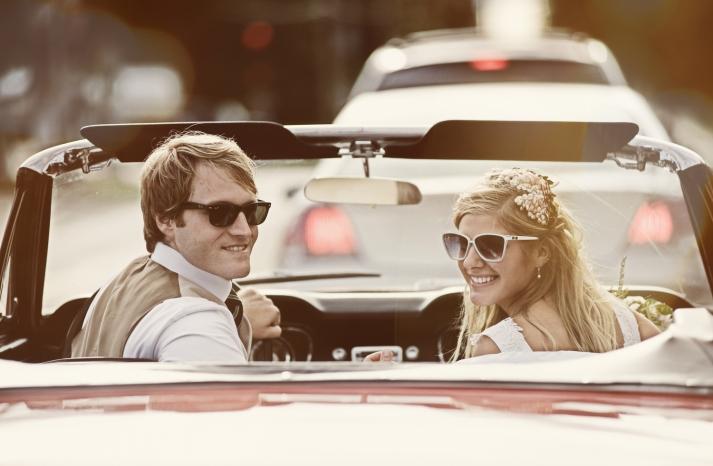 Retro bride and groom drive off in antique ride