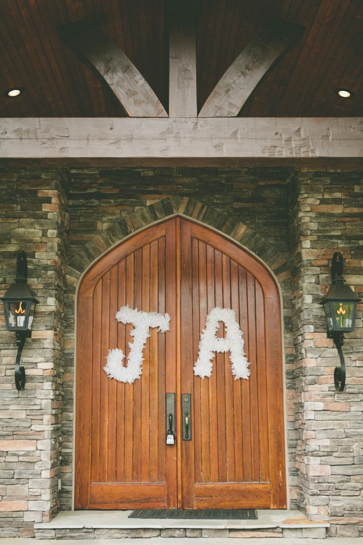 White floral initials hang on wedding ceremony doors